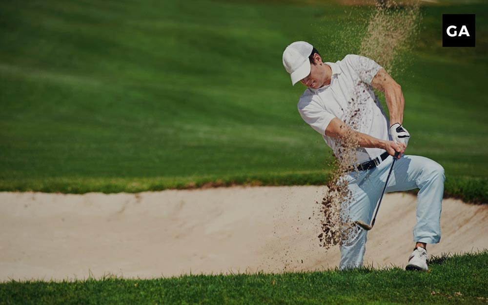 man playing a shot out of a bunker