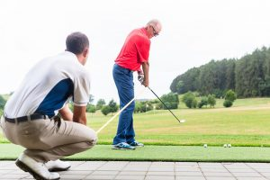 older man getting coached with his golf swing at the driving range