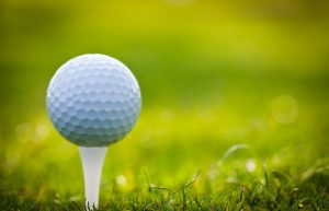 golf ball on a tee on the grass