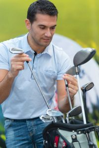 male golfer inspecting long irons and hybrids