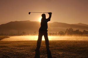 golfer swinging driver as the sun sets