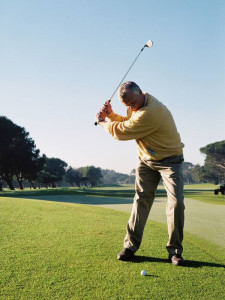 man at top of golf swing