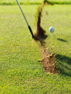 Golf Ball being hit with divet flying