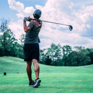 Look from behind a man shut a golf ball on back foot