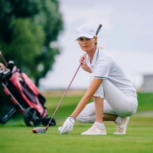 woman squatting on a golf ground thinking about next hit shut